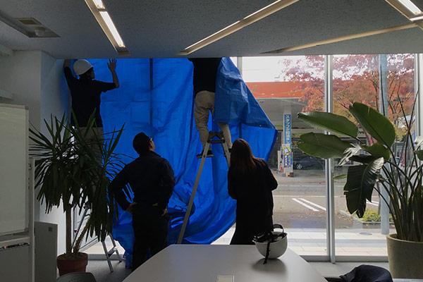 【防災訓練】社屋のガラスが割れた想定で、ブルーシートを設置中。